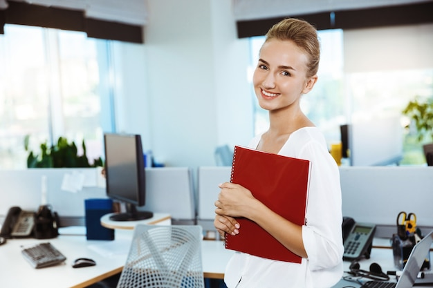 Młody piękny pomyślny bizneswoman ono uśmiecha się, pozuje, trzyma falcówkę, nad biurem