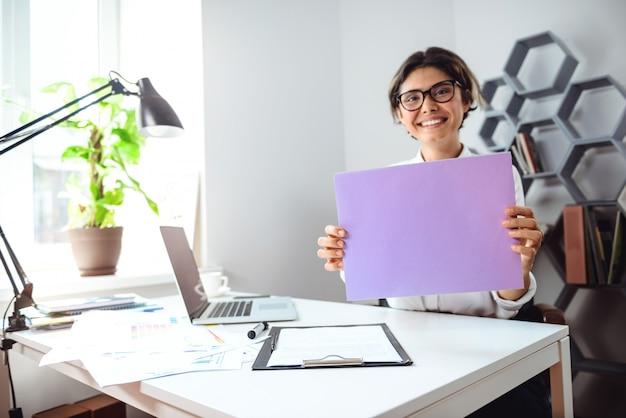Młody piękny rozochocony bizneswoman ono uśmiecha się, trzymający papier przy miejscem pracy w biurze.