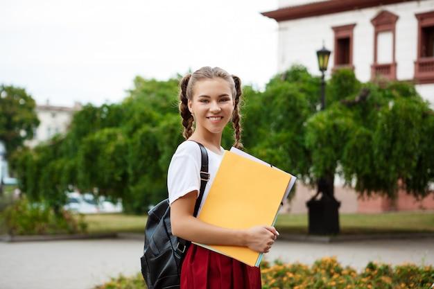 Młody piękny rozochocony żeński uczeń ono uśmiecha się, trzymający falcówki outdoors.