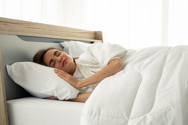 Młody piękny sen w łóżku w domu.