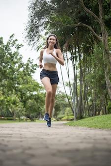 Młody piękny sport kobiety bieg przy parkiem. koncepcja zdrowia i sportu.