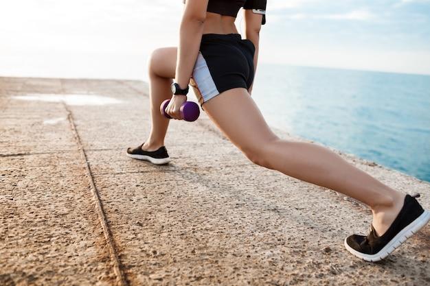 Młody piękny sportive dziewczyna szkolenia o wschodzie słońca nad morzem.
