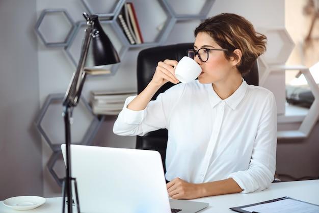Młody piękny ufny bizneswoman pije kawę przy miejscem pracy w biurze.