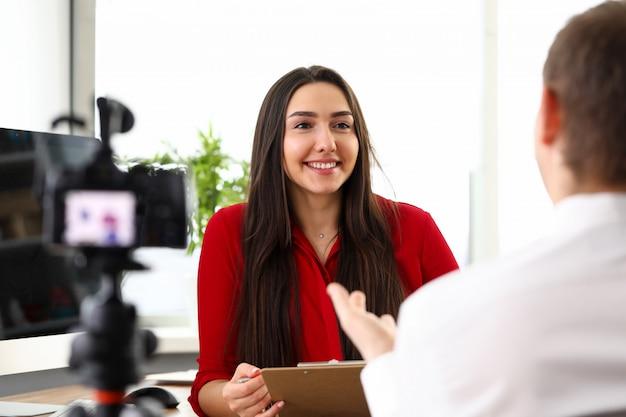 Młody piękny uśmiechnięty brunetki kobiety kierownika obsiadanie w biurze i opowiadać z kolegą lub szefem z kamerą blisko. biznesowa dama, sekretarka, ludzie w biurowym pojęciu