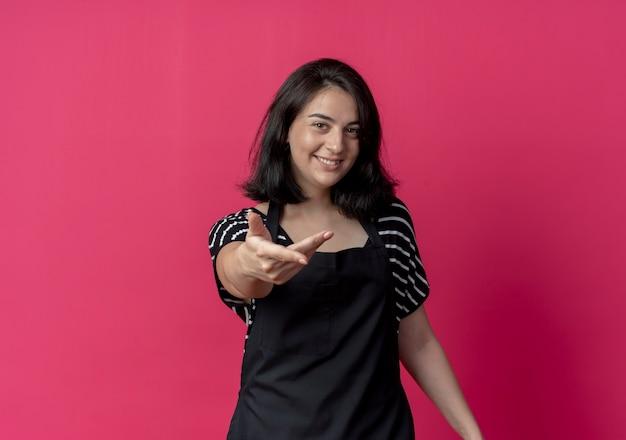 Młody piękny żeński fryzjer w fartuchu co chodź tu gest ręką uśmiechnięty stojący nad różową ścianą