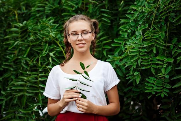 Młody piękny żeński uczeń ono uśmiecha się w szkłach, pozuje nad liśćmi outdoors.