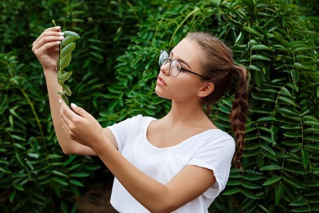 Młody piękny żeński uczeń w szkłach pozuje nad liśćmi outdoors.