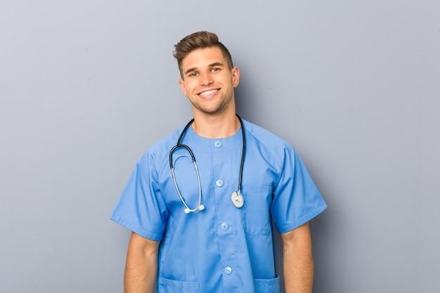 Młody pielęgniarka człowiek szczęśliwy, uśmiechnięty i wesoły.