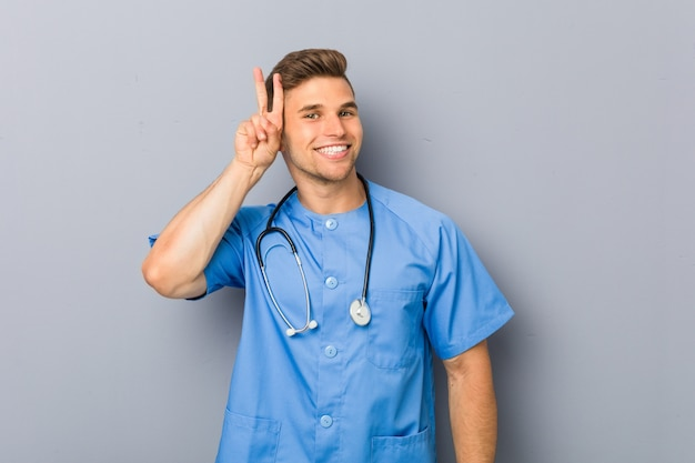 Młody pielęgniarka mężczyzna pokazuje zwycięstwo znaka i uśmiecha się szeroko.