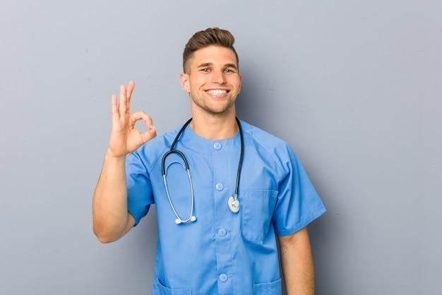 Młody pielęgniarka mężczyzna rozochocony i ufny pokazuje ok gest.