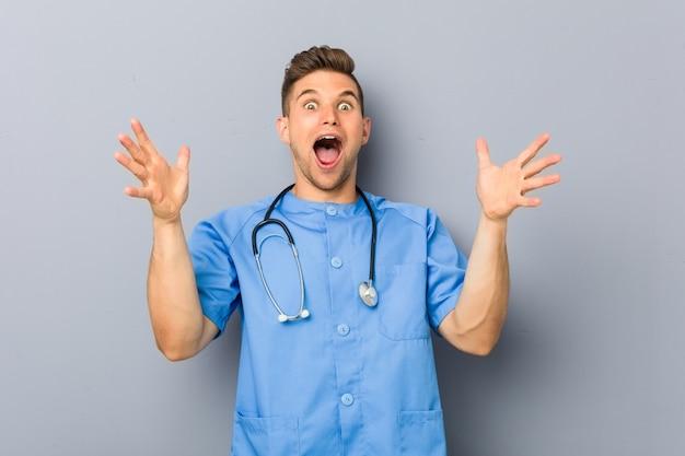 Młody pielęgniarka mężczyzna świętuje zwycięstwo lub sukces