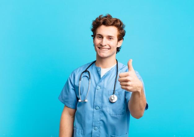 Młody pielęgniarz czuje się dumny, beztroski, pewny siebie i szczęśliwy, uśmiechając się pozytywnie z kciukami w górę