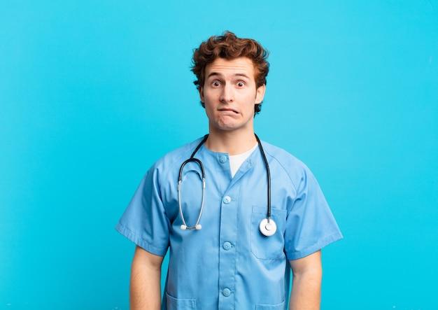 Młody pielęgniarz wyglądający na zdziwionego i zdezorientowanego, przygryzający wargę nerwowym gestem, nie znający odpowiedzi na problem