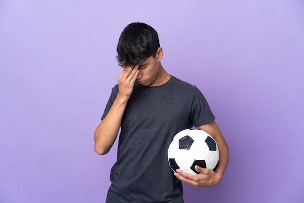 Młody piłkarz mężczyzna na białym tle fioletowy z wyrazem zmęczony i chory