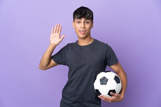 Młody piłkarz mężczyzna na pojedyncze fioletowe ściany salutowanie ręką z happy wypowiedzi