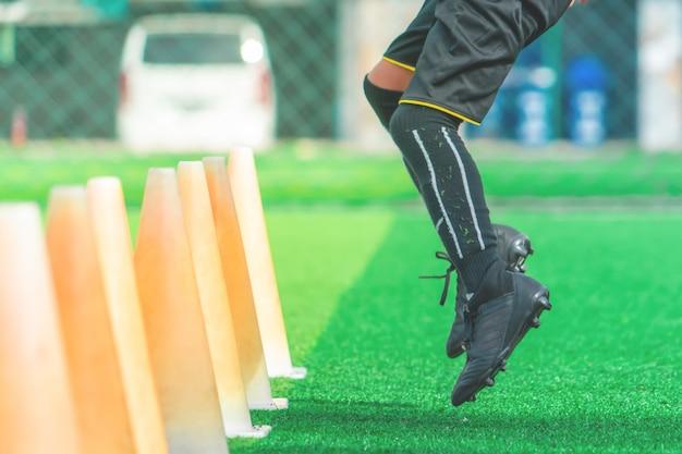 Młody piłkarza szkolenie na boisku piłkarskim