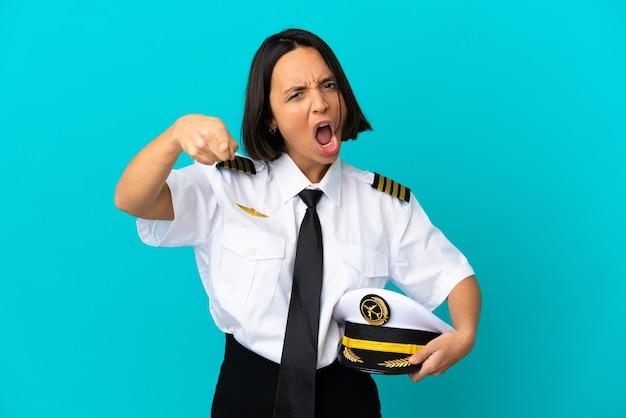 Młody pilot samolotu na odosobnionym niebieskim tle sfrustrowany i wskazujący na przód