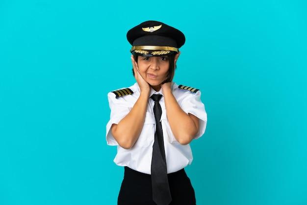 Młody pilot samolotu na odosobnionym niebieskim tle sfrustrowany i zakrywający uszy