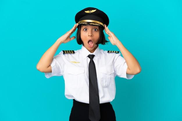 Młody pilot samolotu na odosobnionym niebieskim tle z wyrazem zaskoczenia