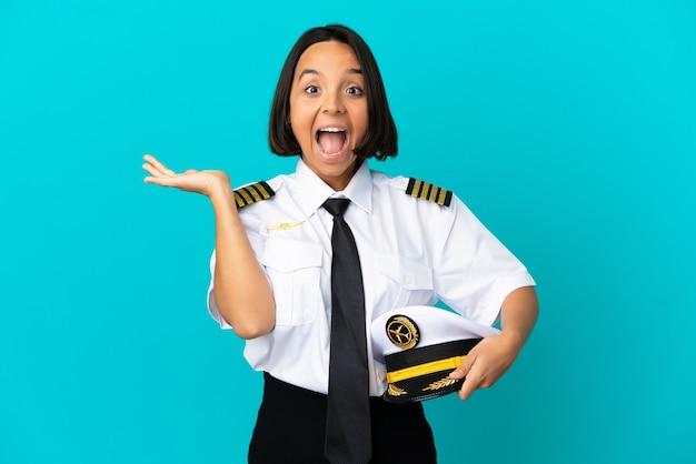 Młody pilot samolotu na odosobnionym niebieskim tle ze zszokowanym wyrazem twarzy