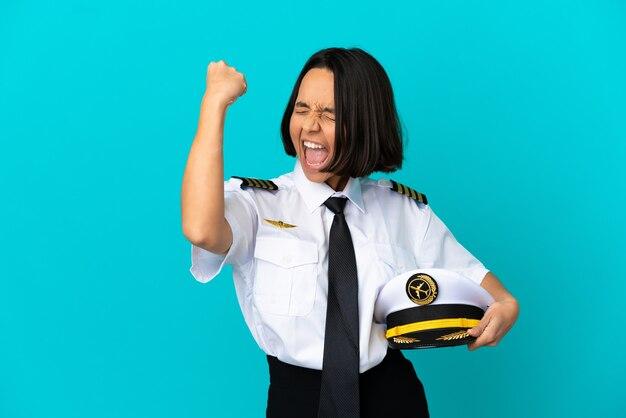 Młody pilot samolotu świętujący zwycięstwo na odosobnionym niebieskim tle
