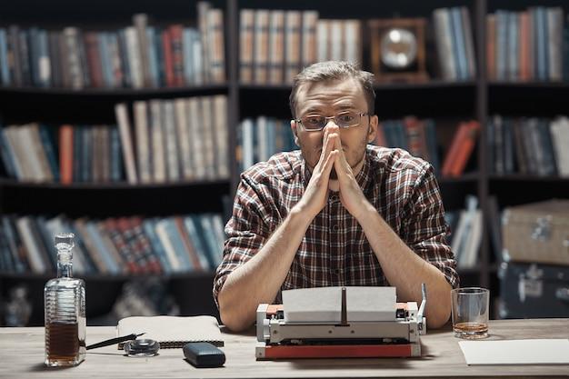 Młody pisarz w okularach siedzi w zamyśleniu przed swoją maszyną do pisania