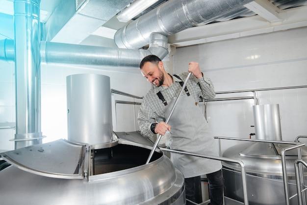Młody piwowar męski zajmuje się procesem warzenia piwa w małym browarze. produkcja piwa.