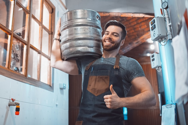Młody piwowar w fartuchu trzyma beczkę