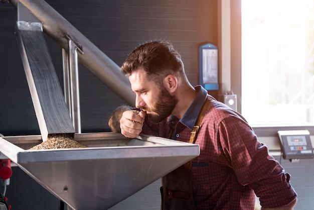 Młody piwowar w skórzanym fartuchu kontroluje mielenie nasion słodu w młynie w nowoczesnym browarze