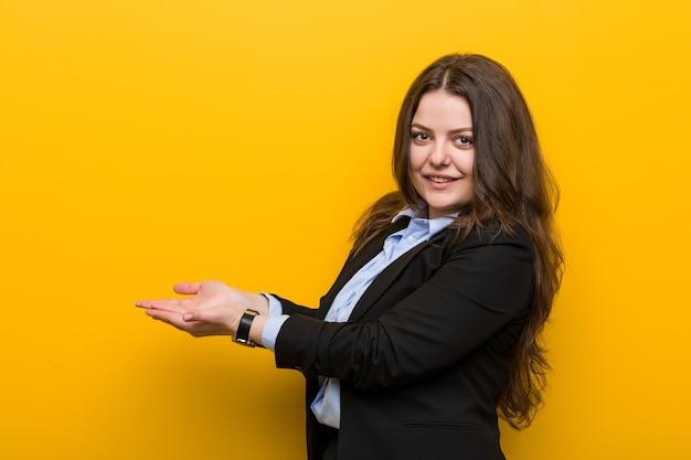 Młody plus rozmiar kaukaski kobieta biznesu trzyma kopię miejsca na dłoni.