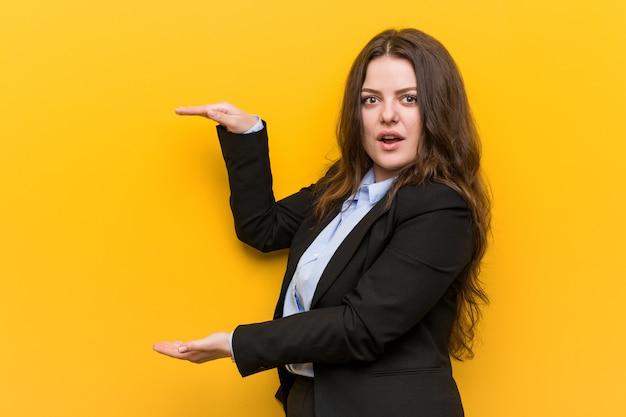 Młody plus rozmiar kaukaski kobieta biznesu zszokowany i zdumiony, trzymając kopię przestrzeni między rękami.