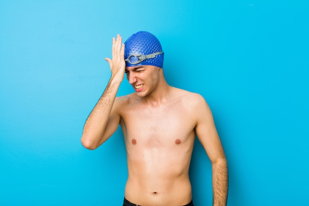 Młody pływak zapominając o czymś, uderzając dłonią w czoło i zamykając oczy.