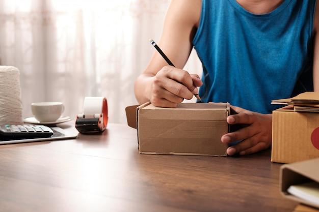 Młody początkujący właściciela firmy writing adres na kartonie w domu