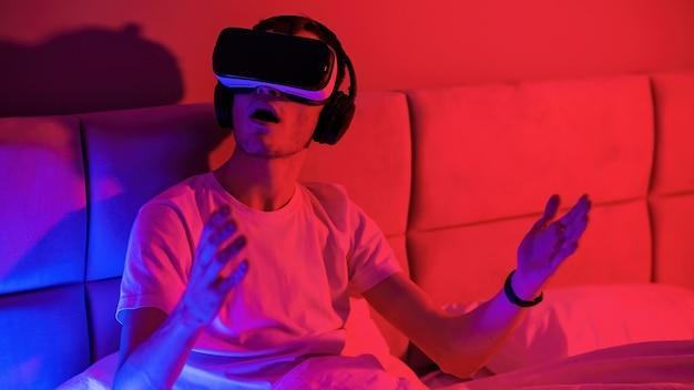 Młody pod wrażeniem mężczyzna w okularach wirtualnej rzeczywistości z niebiesko-czerwonym podświetleniem w pokoju na łóżku. rozrywka w domu
