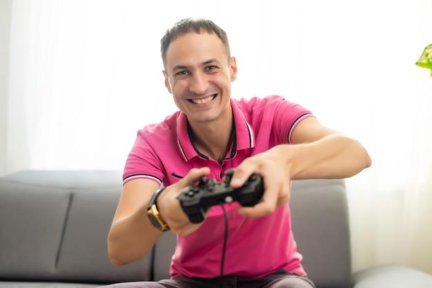 Młody podekscytowany mężczyzna w domu siedzi na kanapie w salonie, grając w gry wideo za pomocą zdalnego joysticka z dziwacznym wyrazem twarzy, bawiąc się uzależnieniem od gier