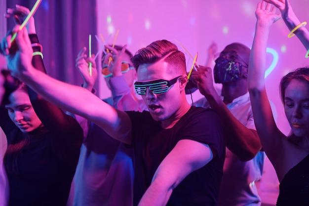 Młody podekscytowany mężczyzna w okularach casualwear i disco oraz jego międzykulturowi przyjaciele ze świecącymi kijami tańczącymi razem, ciesząc się domową imprezą