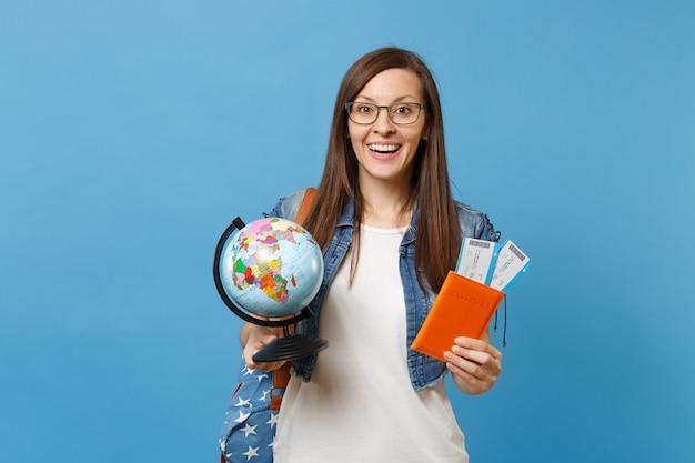 Młody podekscytowany studentka kobieta w okularach z plecakiem trzymając paszport rękawiczki świata, bilety na pokład na białym tle na niebieskim tle. kształcenie na uczelniach wyższych za granicą. koncepcja lotu podróży lotniczych.