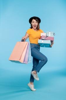 Młody podekscytowany zakupoholiczka z pudełkami na prezenty i papierowymi torbami poruszającymi się w izolacji po sezonowej wyprzedaży
