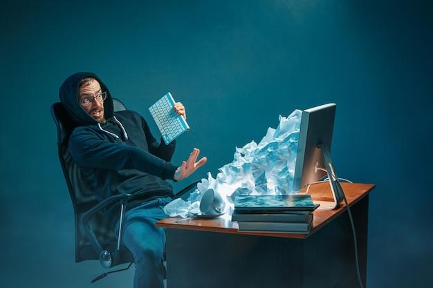 Młody podkreślił przystojny biznesmen pracujący przy biurku w nowoczesnym biurze krzyczy na ekranie laptopa i jest zły na spam