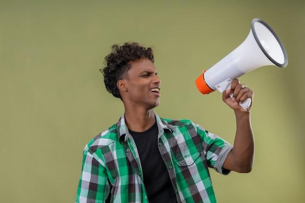 Młody podróżnik african american krzyczy do megafonu stojącego na zielonym tle