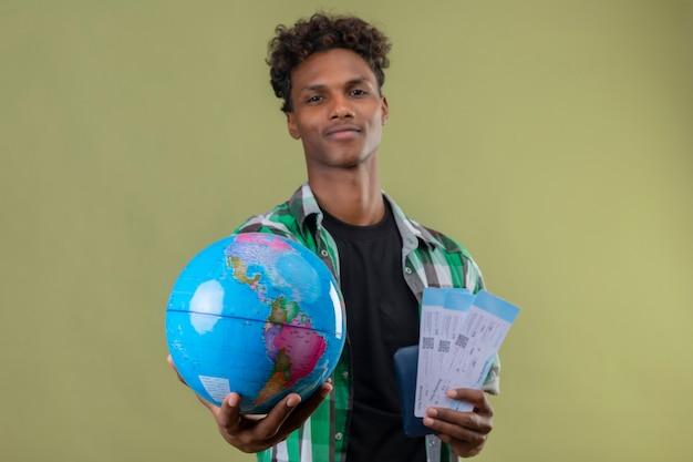 Młody podróżnik afroamerykanin posiadający bilety lotnicze i kula ziemska, rozciągając go do kamery, patrząc pewnie, uśmiechając się