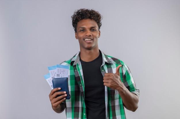 Młody podróżnik afroamerykanin posiadający bilety lotnicze uśmiechnięty radośnie pozytywny i szczęśliwy patrząc na kamery pokazując kciuki stojąc na białym tle