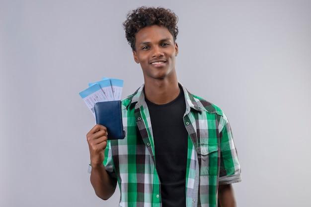 Młody podróżnik afroamerykanin posiadający bilety lotnicze uśmiechnięty wesoło pozytywne i szczęśliwe patrząc na aparat stojący na białym tle