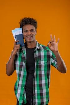 Młody podróżnik afroamerykanin posiadający bilety lotnicze uśmiechnięty wesoło pozytywnie i szczęśliwie patrząc na kamery robi ok znak stojący na pomarańczowym tle