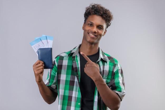Młody podróżnik afroamerykanin posiadający bilety lotnicze wskazując palcem do nich uśmiechnięty wesoło pozytywne i szczęśliwe stojąc na białym tle