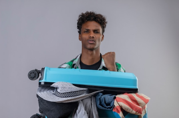 Młody podróżnik afroamerykanin z walizką pełną ubrań podnosząc pięść, patrząc pewnie, ciesząc się swoim sukcesem stojąc na białym tle