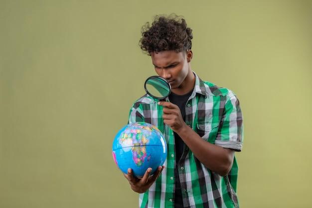 Młody podróżnik afroamerykanów mężczyzna trzyma kulę ziemską patrząc na to przez szkło powiększające z zainteresowaniem stojąc na zielonym tle