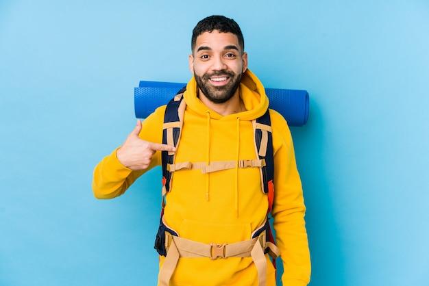 Młody podróżnik arabski backpacker mężczyzna na białym tle osoba wskazująca ręcznie do miejsca kopiowania koszuli, dumny i pewny siebie