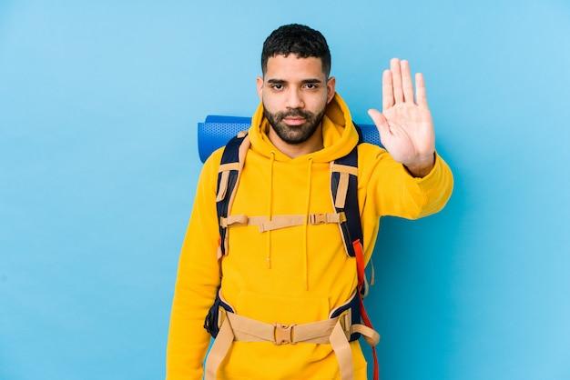 Młody podróżnik arabski backpacker mężczyzna na białym tle stojący z wyciągniętą ręką pokazując znak stop, zapobiegając ci.