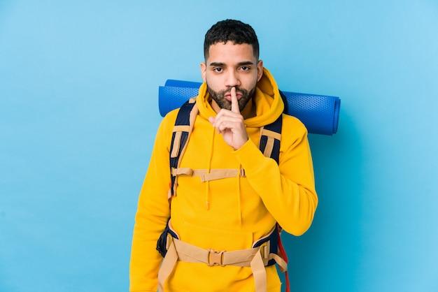 Młody podróżnik arabski backpacker mężczyzna na białym tle utrzymanie w tajemnicy lub prosząc o ciszę.